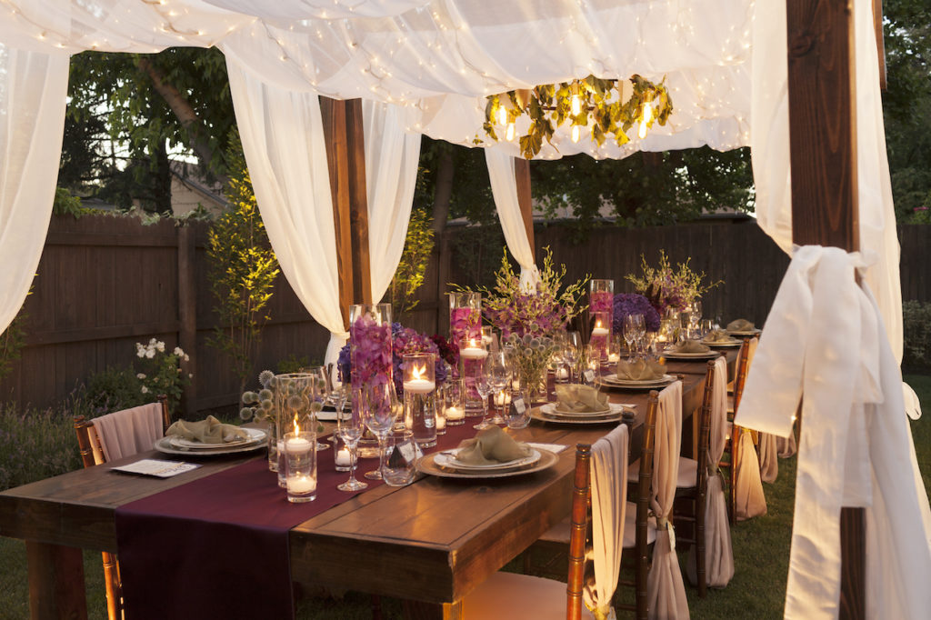 An outdoor table glows under candlelight, covered by a linen wrapped gazebo decked out in flowers and greenery.