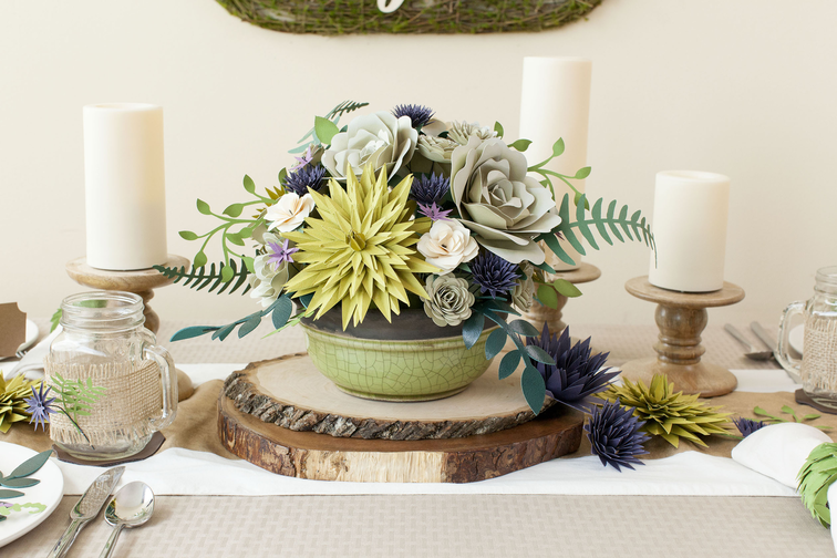 A bowl of green paper flowers and plants sits atop a wooden table centerpiece, surrounded by rustic candles.