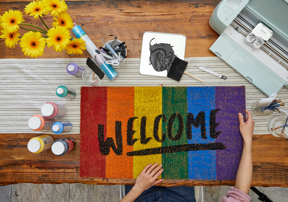 A pair of hands holds a welcome mat that reflect the rainbow colors of the gay Pride flag.