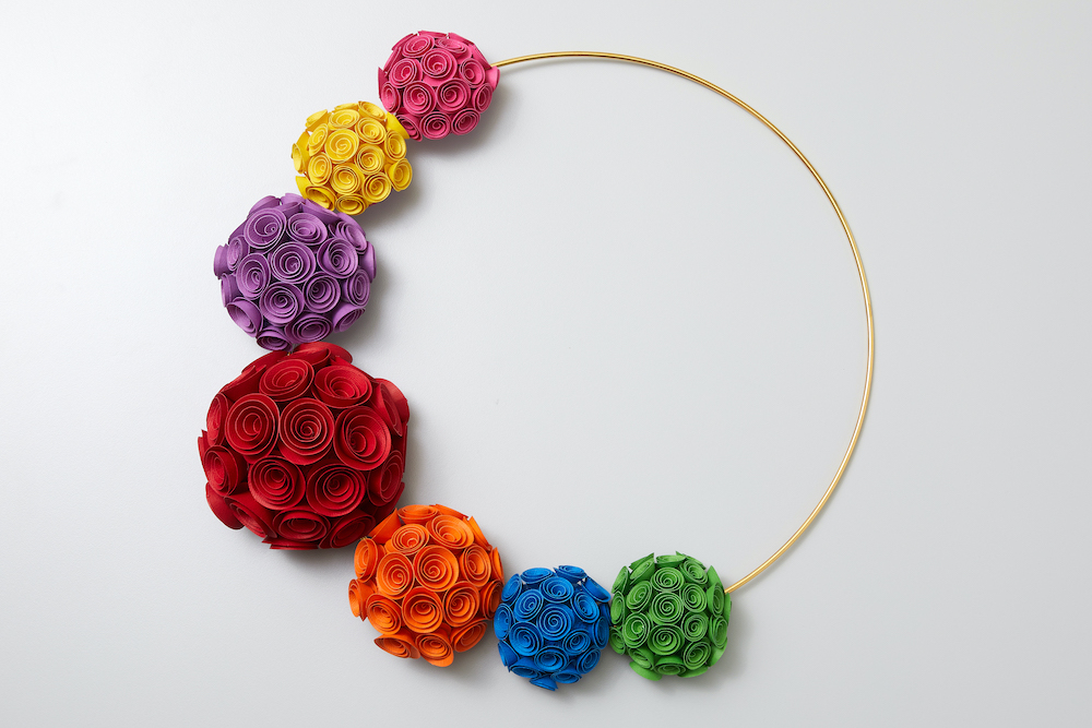 A rainbow colored wreath made of rolled paper roses hangs along a white wall.