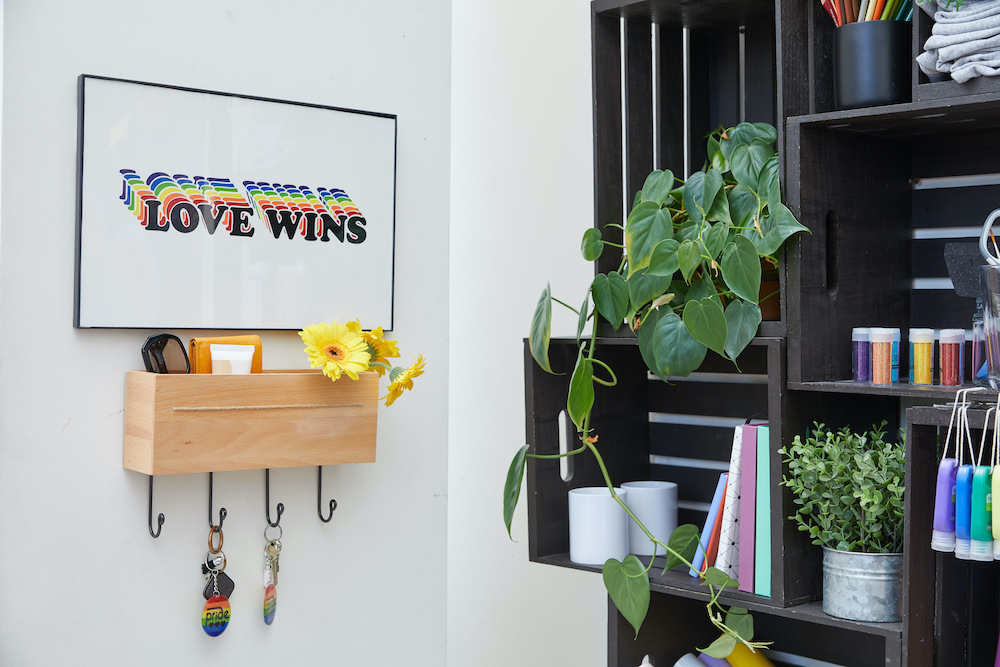 """A graphic rainbow pop art of the phrase """"love wins"""" sits on a white wall next to a black crafting shelf and key holder."""