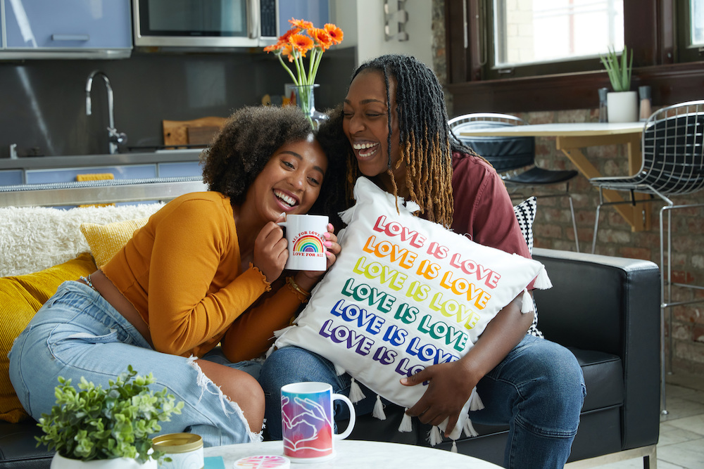 """Two people sit together laughing on a couch, holding a white pillow that reads """"love is love"""" in various colors."""