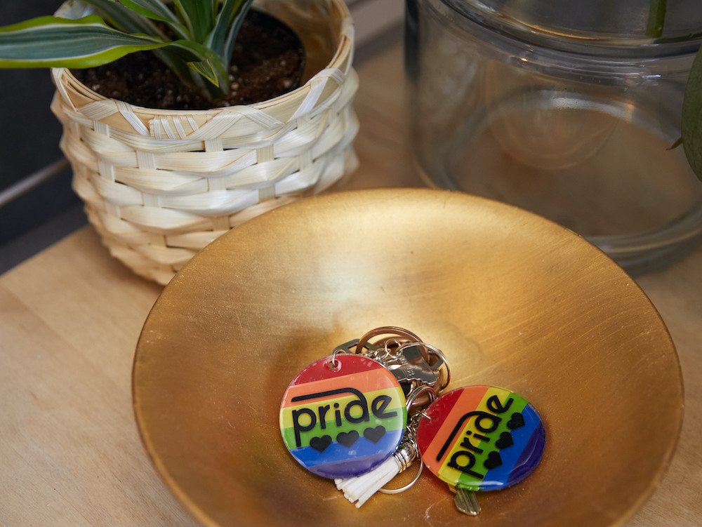 Two rainbow colored pride keychains sit in a gold catch-all dish.