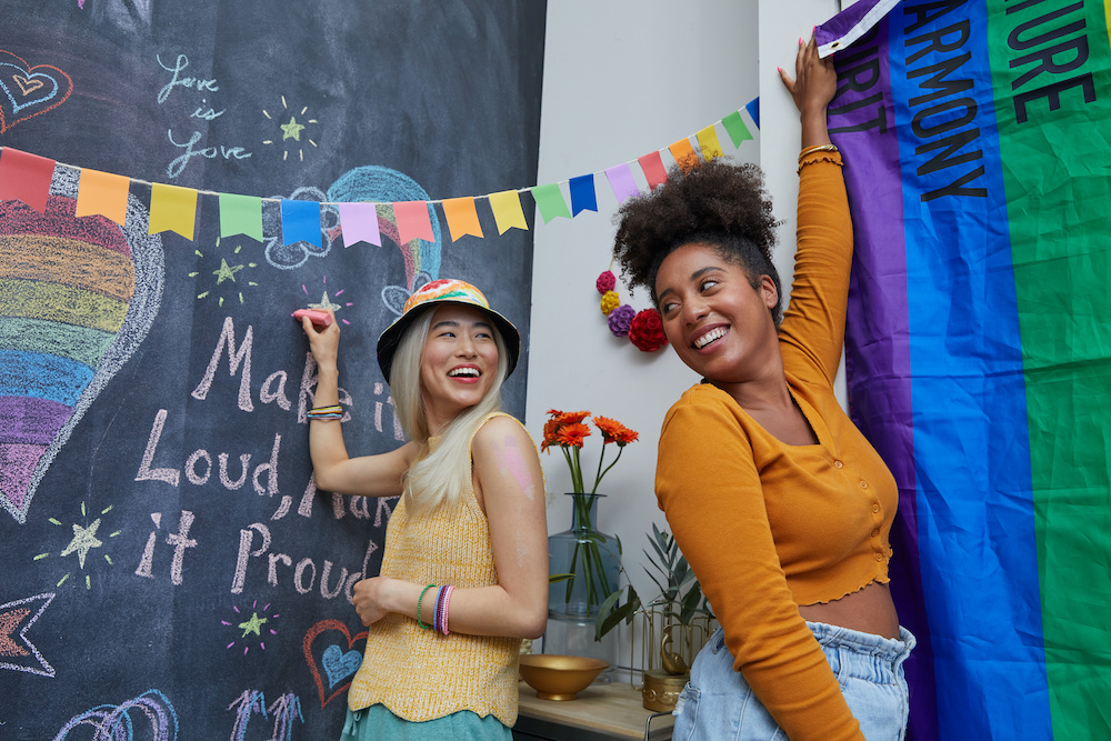 Two people decorate their apartment walls with rainbow colored decor to celebrate Pride month