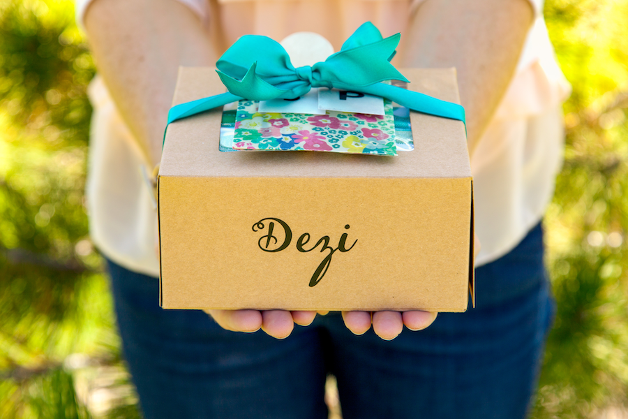 A woman holds out a customized picnic box with a blue bow on it