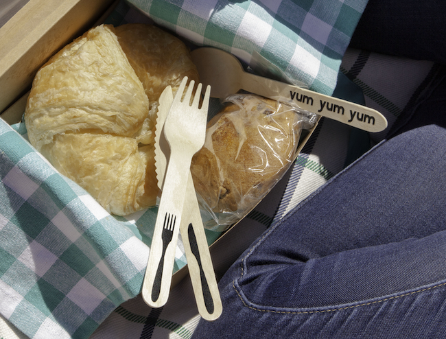 Wooden cutlery sits inside a picnic box, next to a croissant and muffin