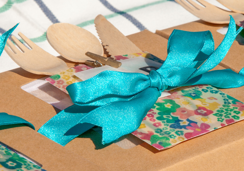 Wooden cutlery is nestled inside a floral paper sleeve, topped with a blue bow