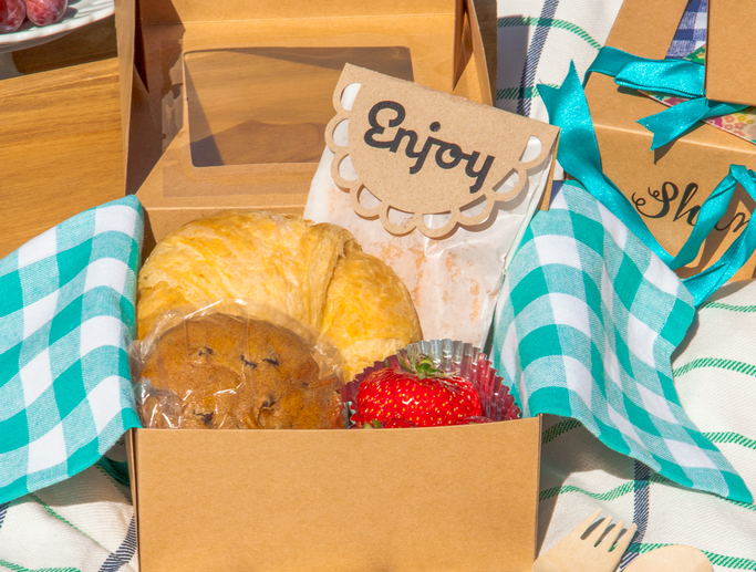 Fruits and pastries sit inside a cardboard picnic box with a blue gingham napkin