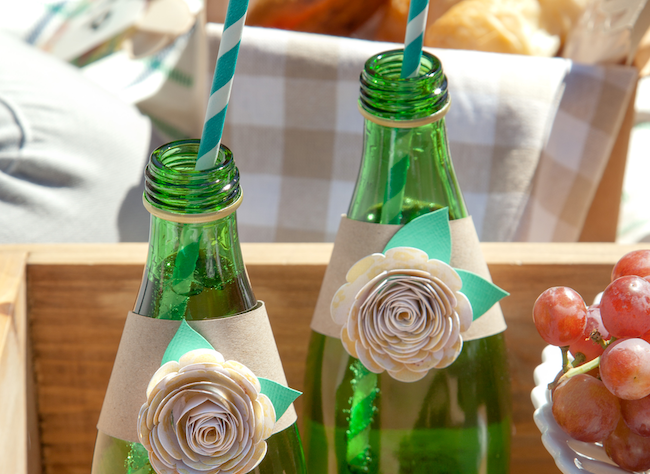 Green glass water bottles are wrapped with paper flower embellishments
