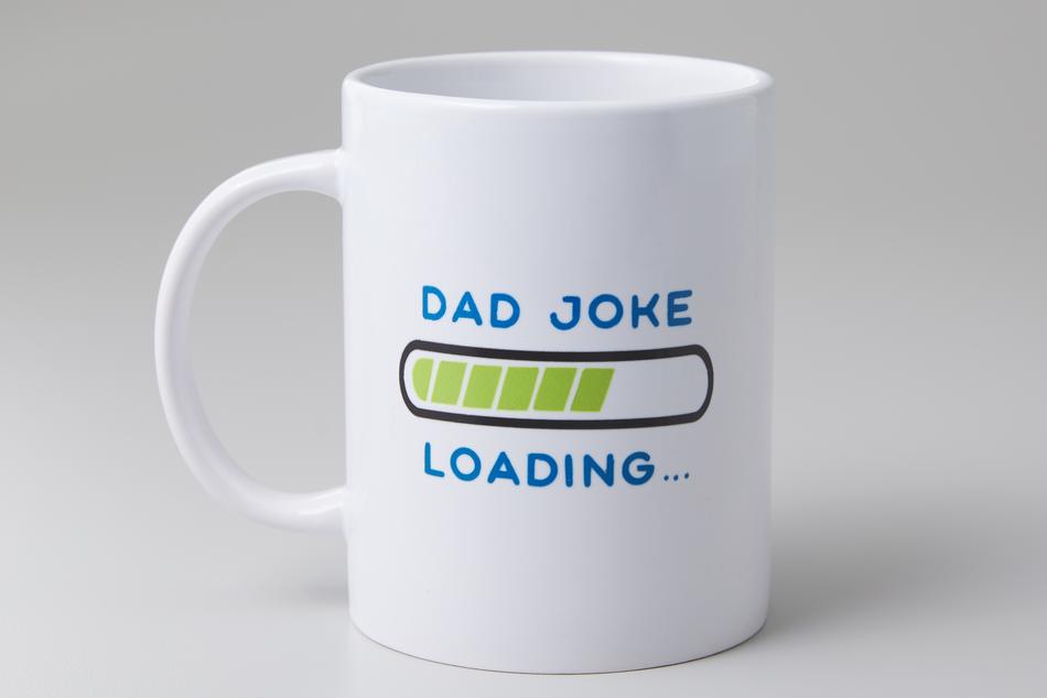 "A white mug reading ""dad joke loading"" sits on an off-white background."