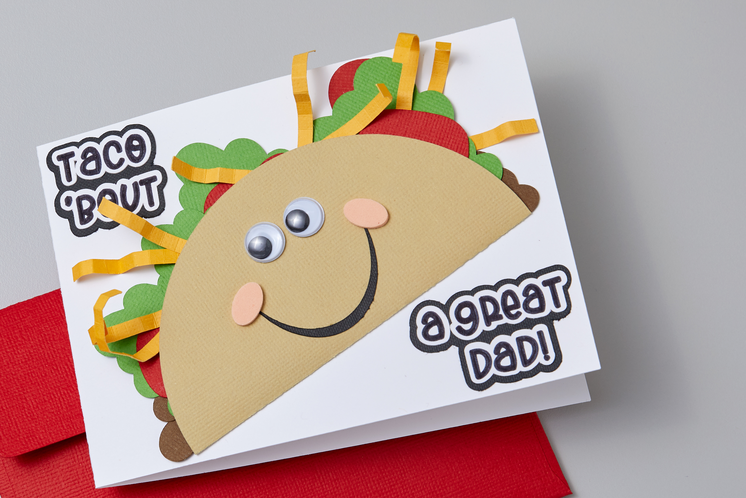 """A cute Father's Day card reading """"taco bout a great dad"""" sits on a table"""