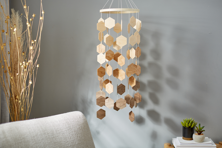 A wooden hanging mobile is suspended from the ceiling of a boho bedroom
