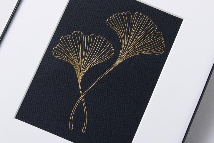 Golden line art of a gincko flower is impressed upon a black canvas