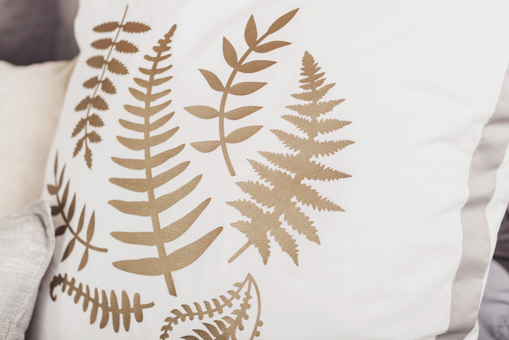 A leather golden leaf pattern on a white pillow