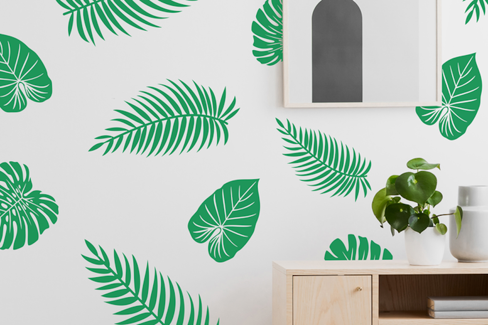 A green pattern of palm leaves on a white wall
