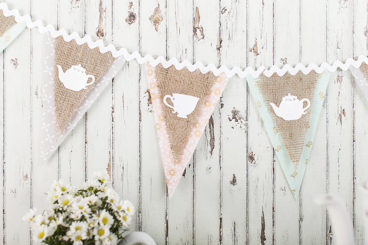 A burlap and pastel colored banner with tea party motifs sits on a farmhouse wall