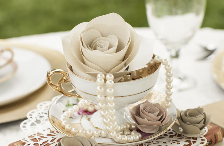 A white tea cup is surrounded by neutral colored paper roses and pearls
