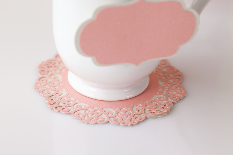 A white teacup sits on a pink lacey paper design