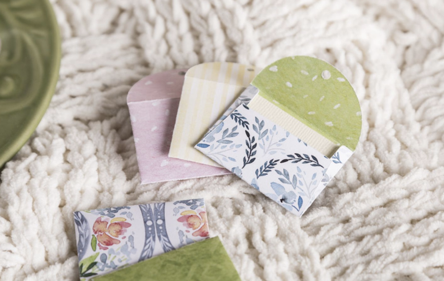 Floral tea bags sit on a white blanket