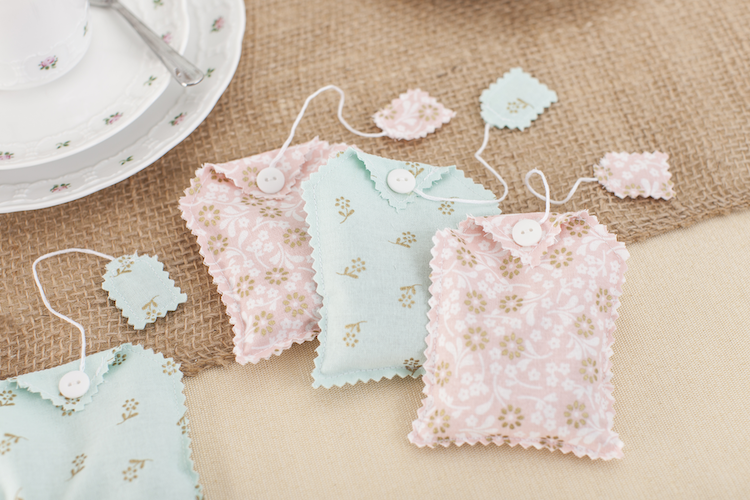Fabric tea bag sachets in pink and blue sit on a brown table