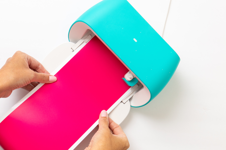 Hands feed pink Cricut vinyl into the Cricut Joy cutting machine