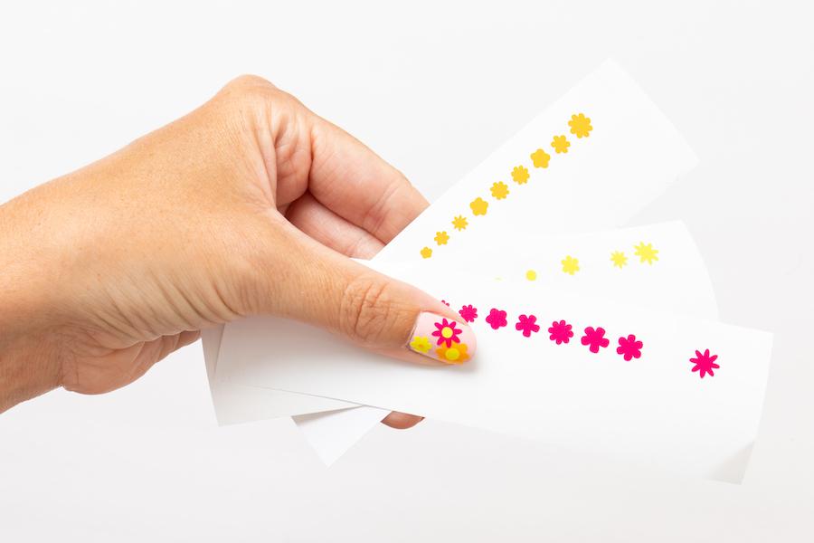 A hand displays a summer nail design created using Cricut permanent vinyl smart material