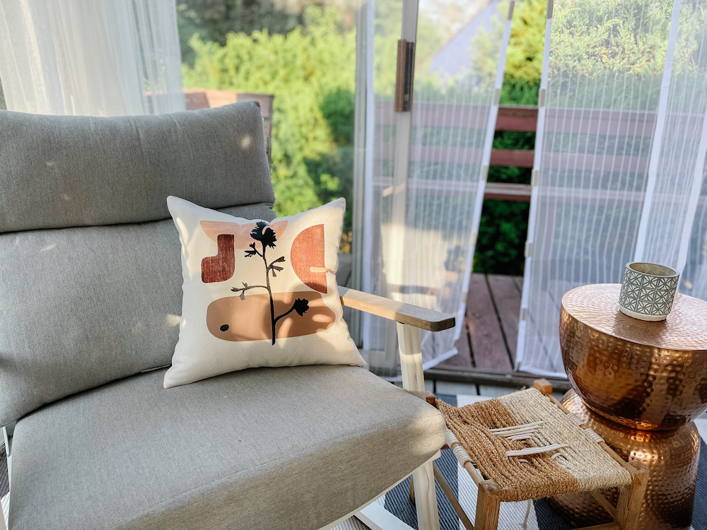 A contemporary, organic modern pillow created with Cricut sits on a grey outdoor chair