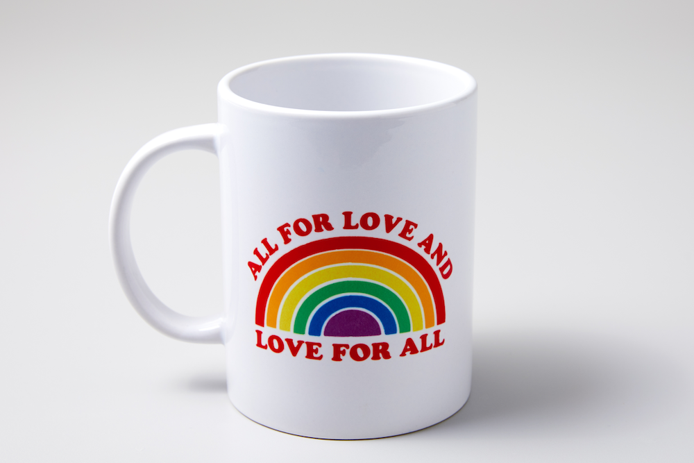 """A white mug with a design reading """"all for love and love for all"""" around a rainbow decal sits in a white shadowbox."""