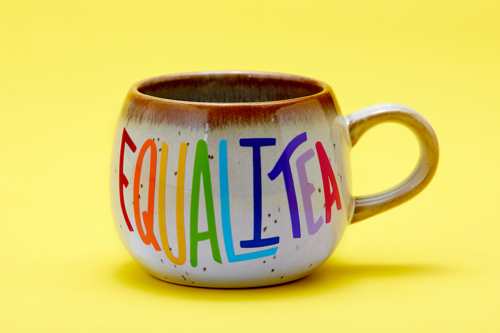 """A brown ceramic mug reading """"equalitea"""" in rainbow lettering sits in a yellow shadowbox"""