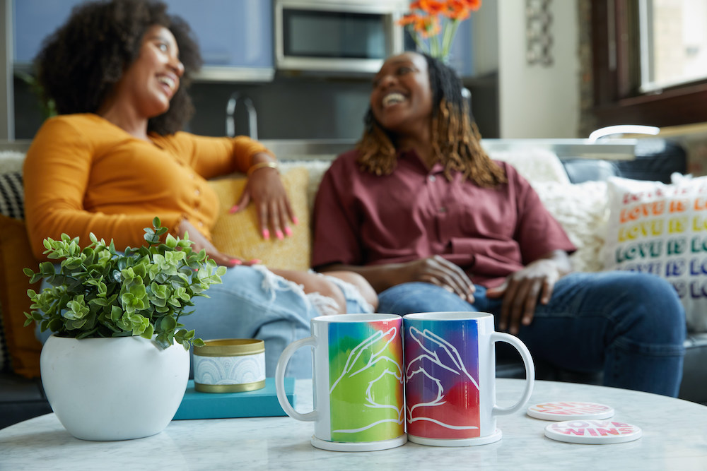 """Two people sit on a couch in the background–in the foreground you see colorful mugs that, when pressed together, form a """"heart hands"""" shape."""