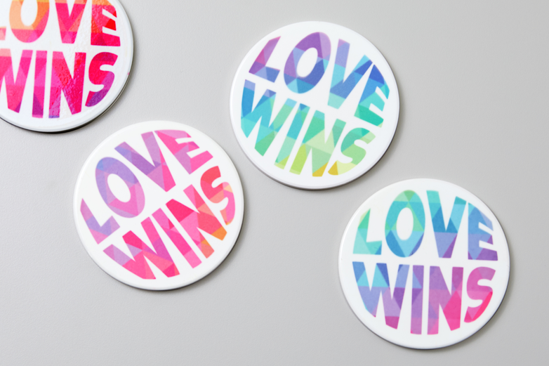 """White coasters reading the phrase """"love wins"""" in rainbow bubble lettering sits on a grey surface."""