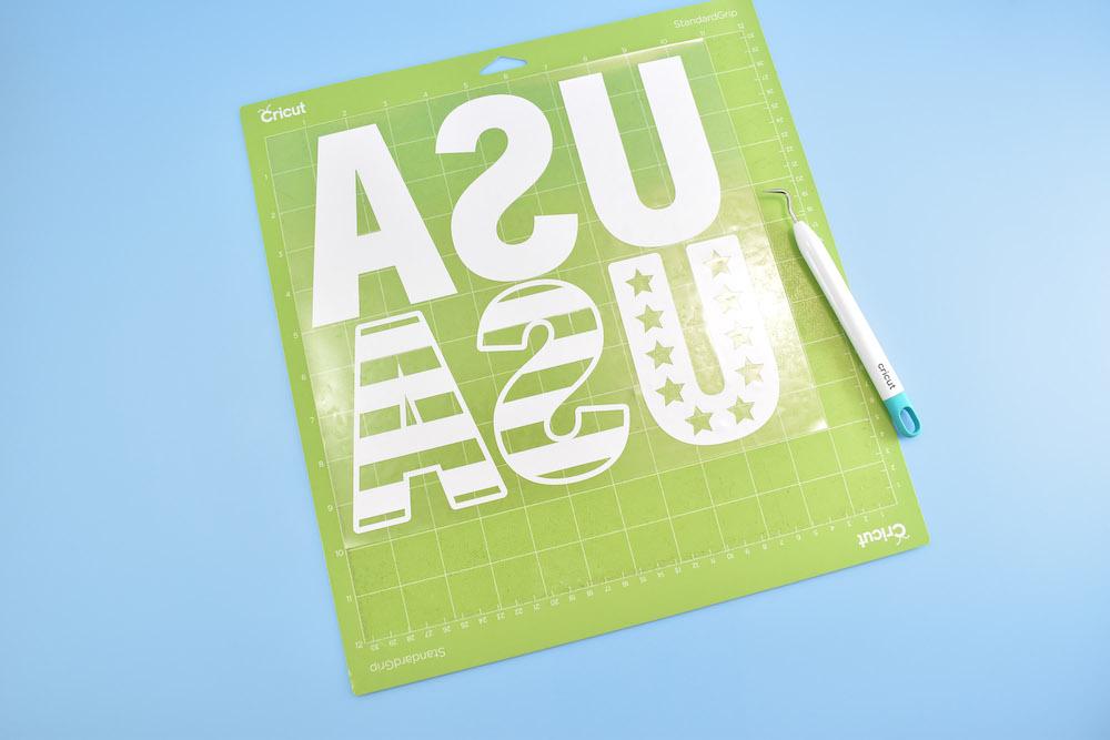 "A ""USA"" design being weeded off of a green Grip mat"