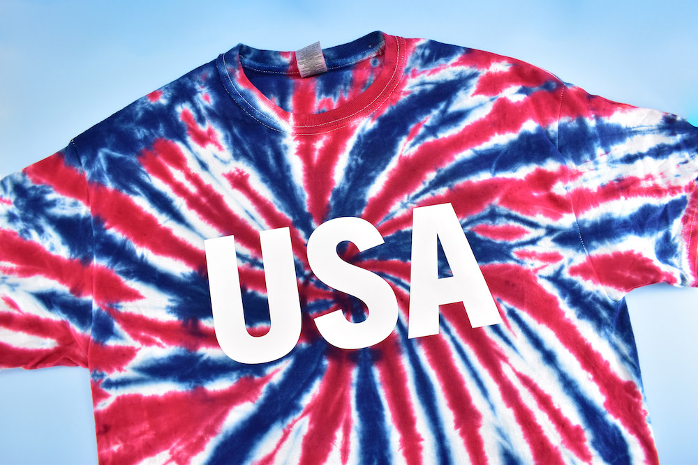 """A finalized, bold white """"USA"""" logo on a red, white and blue tie-dye design"""