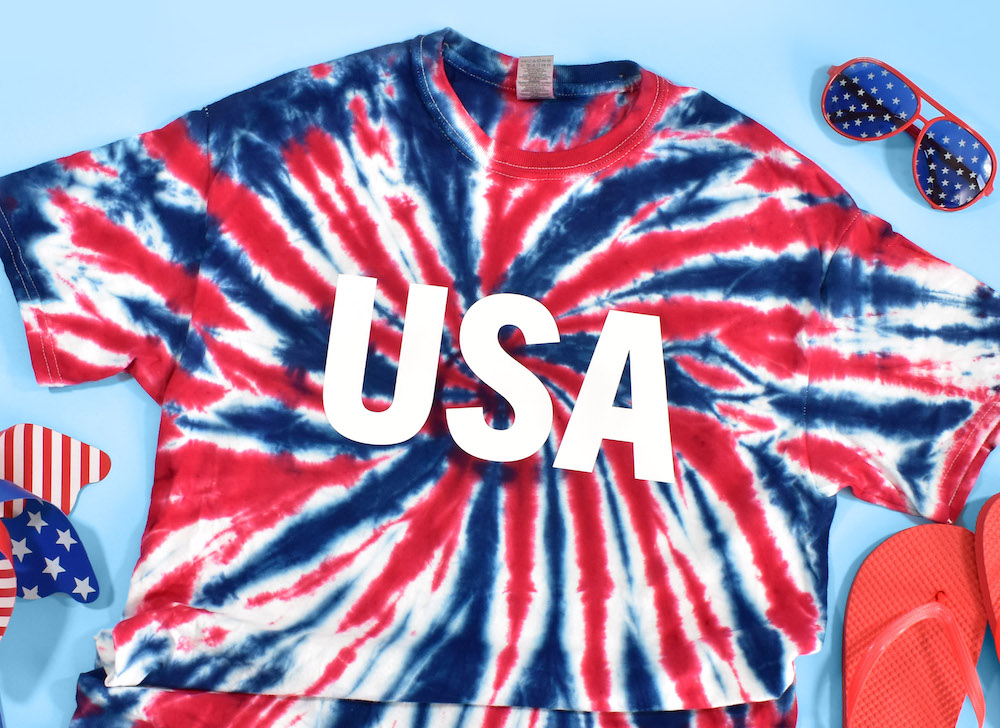 A red, white, and blue tie-dyed USA t-shirt for the 4th of July is surrounded by patriotic flip flops and sunglasses