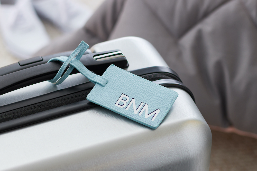 A blue monogrammed luggage tag sits on a silver rolling suitcase