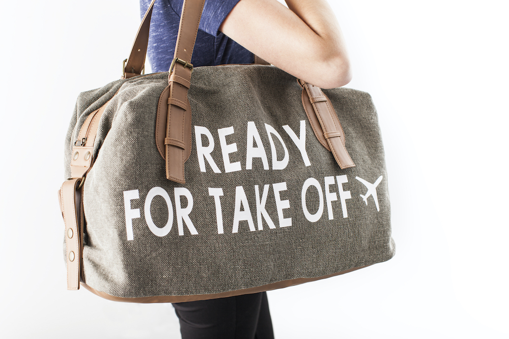 """A personalized, brown carry-on canvas duffel has a design that reads """"ready for takeoff"""" in white iron-on vinyl"""
