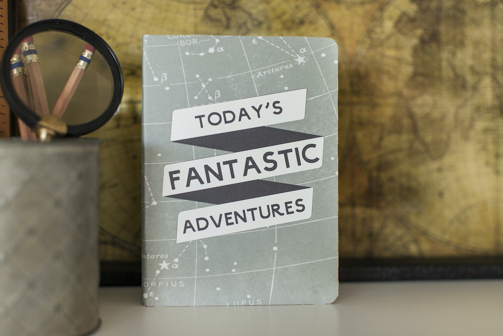 """A light blue travel notebook has the phrase """"today's fantastic adventures"""" on the front cover"""