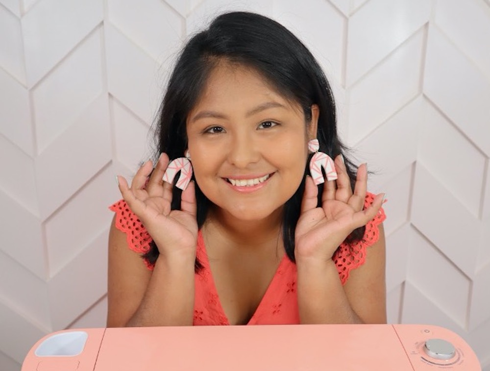 A woman holds polymer clay earrings she made using vinyl Cricut stencils
