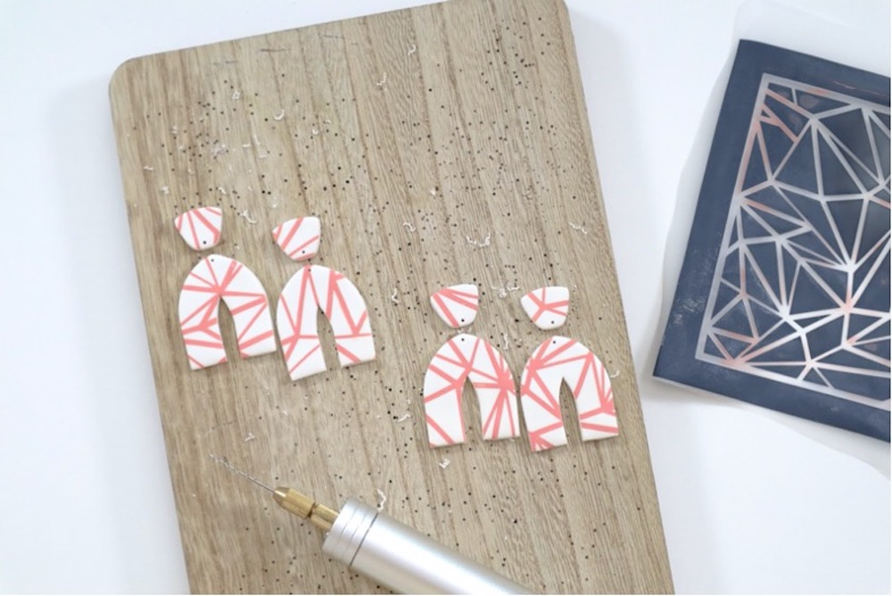 White and pink polymer clay earrings sit on a wood board
