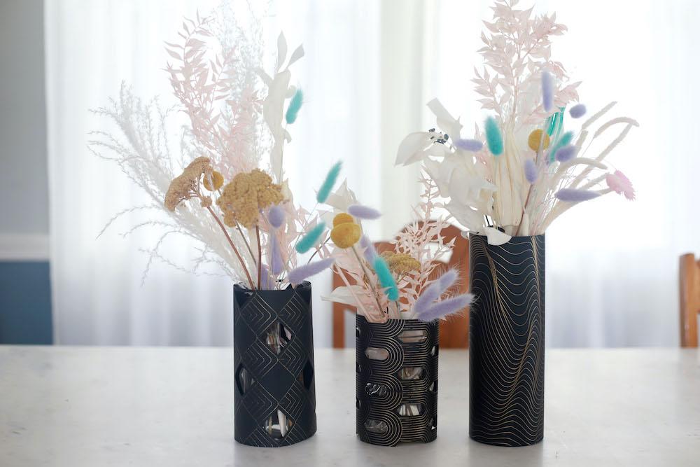 3 pastel colored floral wedding centerpieces sit in Cricut made black paper vase wraps