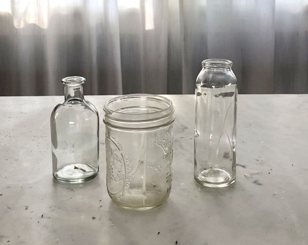 3 glass jars to be repurposed as wedding centerpieces sit on a concrete countertop