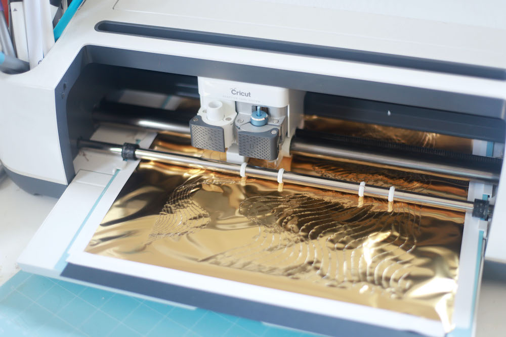 Gold foil being etched onto a piece of black cardstock using a Cricut machine