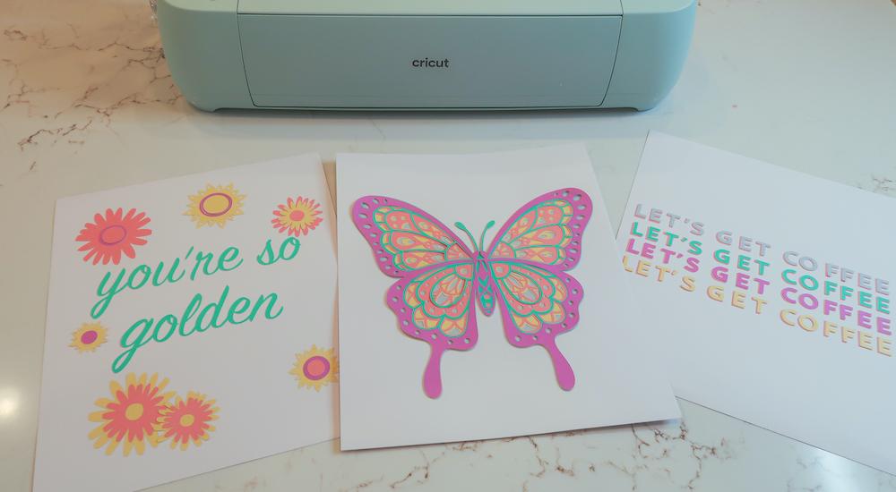 A Cricut Explore Air 3 sits beside 3 colorful, pastel art prints for dorm room decor