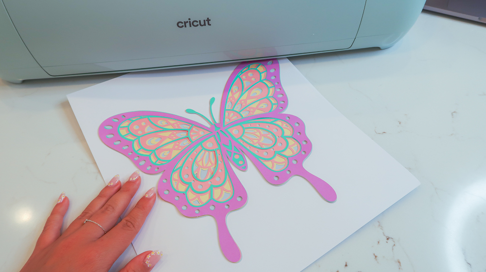 A pastel color butterfly on a piece of white cardstock, designed as dorm room decor