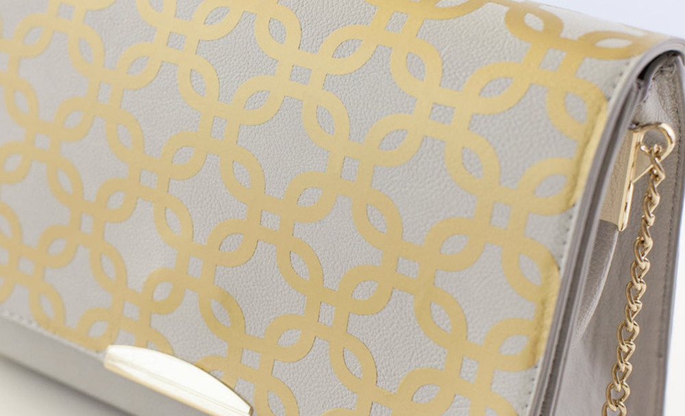 Photo of a grey / nude handbag with gold pattern and embellishments