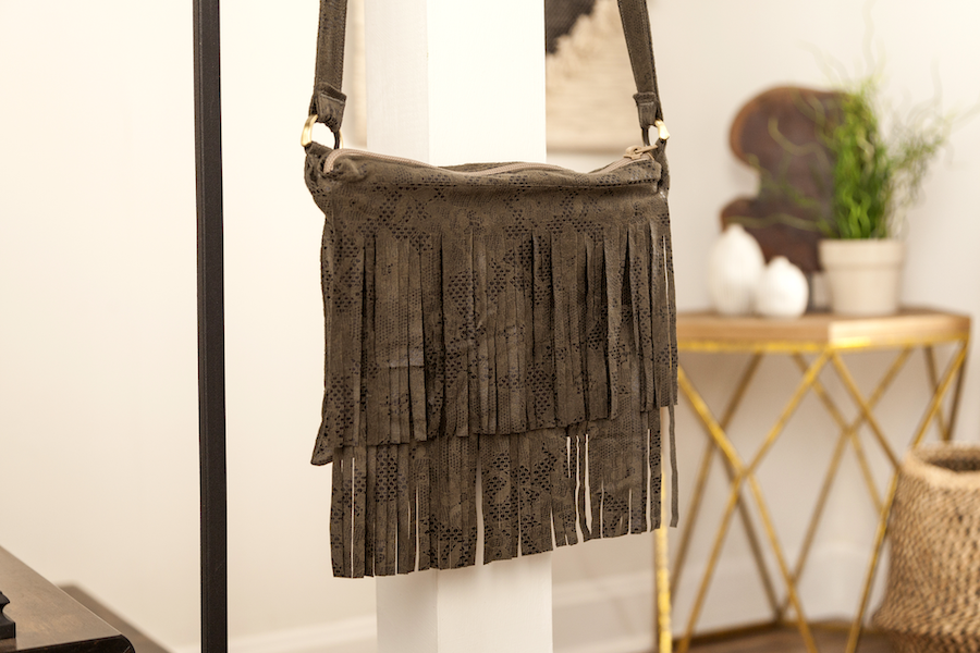 A brown tasseled faux suede handbag hangs from an iron rod
