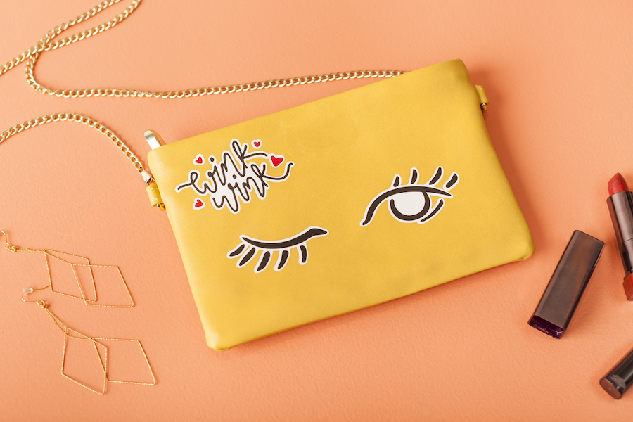A yellow clutch handbag with a winky face design sits on a peach colored background