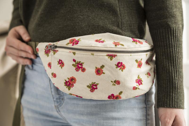 A floral belt bag rests on someone's hip