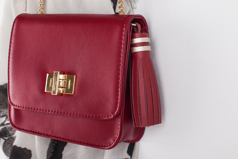 A wine colored handbag with a leather tassel is hung on a wall