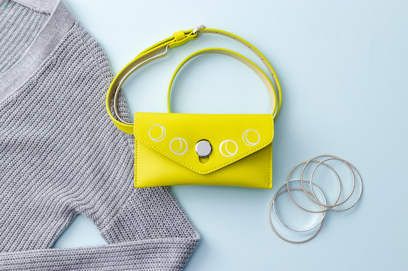A yellow handbag sits on a blue background next to a grey sweater